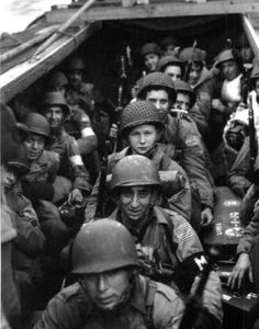 Soldiers, some younger than 18 years old, heading to storm the beaches at Normandy.