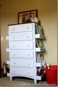 Attach Ikea spice racks to sides of dresser for easy-to-reach book/magazine storage/display