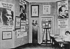 "First International Dada Fair, Berlin, 1920, with Höch's Dada dolls (on pedestal in center) and ""Dada stands beside the revolution- ary Proletariat!"" poster with photograph of Grosz's profile (to right)."