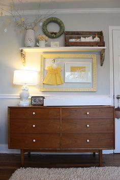 Love the old dresser. love the framed dress. love the high shelf.