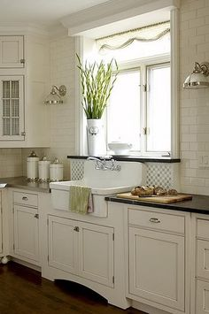 Subway tile to ceiling,lighting side sconces, farmhouse sink/marble window sill/mixed counter space stainless,marble or other stone/glass cabinet fronts with checked material/pops of shiny metals shine like jewelry in an amazingly put together, mostly cream colored kitchen~Photobucket