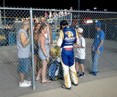 Hendrick Motorsports driver Chase Elliott signs autographs for fans after a NASCAR K Pro Series East race in August.