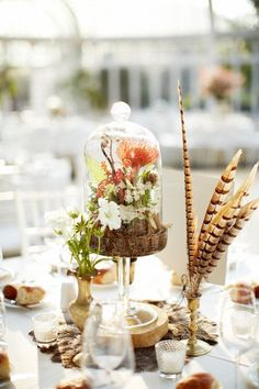 Love the mix of the bell glass terrarium along with the long willowy pheasant feathers | Why It Works Wednesday: 9 Terrariums That Are Prime For The Centerpiece Spotlight http://storyboardwedding.com/9-terrarium-wedding-centerpieces/