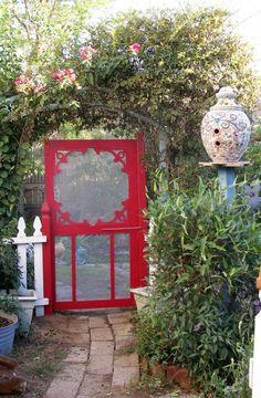 Red screen door used as garden entrance.