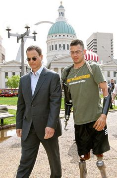 """Marine Cpl. Todd Nicely walks with Actor Gary Sinese. Nicely and his family have moved into a """"smart home"""" in Lake Ozark, MO. built for his physical needs that allows him independence after (during his tour of duty in Afghanistan in 2012) being injured when he stepped on an explosive device that ripped off his hands and lower legs.  Money was raised partially by a concert given by actor Gary Sinise's band to build the house. (credit courtesy of Chris Kuban)"""