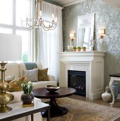 Candice Olson  living room! Fireplace, chandelier, white sectional sofa, gourd lamp, round pedestal coffee table, floral damask pillows, ivory blue rug, white sheers, mirror, sconces, silver metallic floral wallpaper and white blue vases.