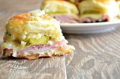 This Funeral Sandwich Casserole is anything but sad. It's made with ham, cheese, and pickles with a creamy dijon sauce. Layered among sweet, fluffy King's Hawaiian rolls and baked, these sandwiches are super easy to bring to a potluck or picnic. Plus, they're just so darn cute.