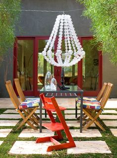 A fun and funky outdoor dining area features an unusual bubble chandelier