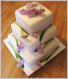 Love calla lilies? If so, you're going to like this 4-tier, square, white fondant weddingcake accented with orchid/lavender satin striped ribbon and accented with pink/lavender/mauve calla lily stems. a unique take on a calla lily cake.
