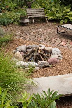 I love how casual this firepit is. Cooking Fire in Backyard with brick patio, fireplace made of stones, with bench and plants
