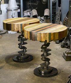 Wood top tables with crankshaft and disc brake rotor bases.