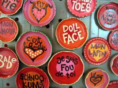"""Pet name magnets"" created on recycled jar lids by Birmingham, Alabama artist Veronique Vanblaere, owner of Naked Art Gallery."