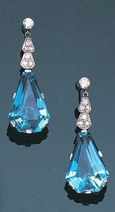 A pair of aquamarine and diamond pendent earrings, circa 1945 Each brilliant-cut diamond surmount suspending geometric motifs of brilliant and single-cut diamonds, terminating in a calf's-head-cut aquamarine, length 3.7cm.