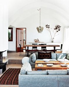 An eclectic mediterranean living room with arched ceilings, pair of grey couches, and wooden coffee tables.