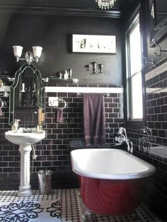 Squeeze a lot of (the good kind of) drama into your tiny bath by going for an all-black decorating scheme. Just give your eye the chance to rest with other colors like here with a white pedestal sink and deep red claw-foot tub.