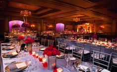 Royal conference-style tables create a lovely formality in the Grand Ballroom at The Ritz-Carlton, Atlanta. Romantic red roses provide a brilliant burst of color against the monochromatic color palette.