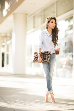 A button-down shirt, boyfriend jeans and a leopard print clutch make for a chic afternoon ensemble