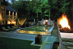 Using tones and textures found in the home, the pool designer created a dramatic infinity pool that includes a lion head fountain, in-pool lighting, exterior lighting, and a spectacular fire wok. Downes Swimming Pool Company, Inc., Arlington, Heights, Illinois; Photography by John P. Frantz http://www.luxurypools.com/builders-designers/downes-swimming-pool-company-inc.aspx