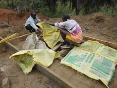 9. The wood and wire are then covered with plastic sheeting, or old cement bags as are being used here.