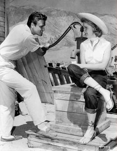 Full BTS shot of John Ericson as Pete Wirth, standing and holding water pump handle, and seated Anne Francis as Liz Wirth.