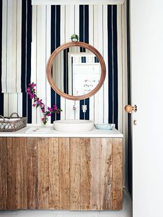 Tour the Ultimate Spanish Vacation Home// stripe walls and a reclaimed wood vanity in a powder room