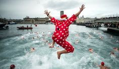 A Spanish reveler jumps into the harbor near Las Ramblas