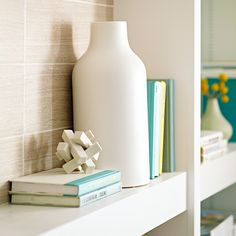 Choose your big visuals first, such as a large print over the firebox, then fill in the rest. Divide book groupings using vases, medallions, and accents. Lay books on their sides to break things up.