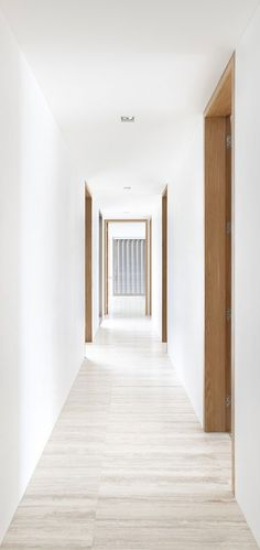 Corridor with wood and travertine. The Boustred House by Ian Moore Architects.