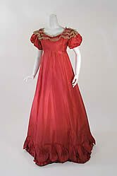 "Raspberry silk ball gown, 1820's. Evening dresses of the 1820s were decorated with all types of fancy borders including rouleaux, the bands of bias cut fabric stuffed with wool or cotton that would provide additional body and shape at the hemline. In addition the hemline is decorated with a pinked silk ruffle above the rouleaux and above that a scalloped flounce accented with satin appliques that appear to be flower buds about to open. The dress has a slightly empire waistline with the bodice fitted with a series of three vertical darts on both sides of the bust. The neckline is rounded and set off by delicate hand made lace and satin trim. The satin is carried around the neckline and extends in layered ""petals"" across the puffed short sleeves. Each petal is edged in lace and the sleeves are decorated with the same bud shapes and scalloped edging as is found at the hemline. Back closure with hooks and eyes. The sleeves are lined with a fine silk gauze."