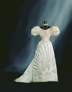 Evening Dress c. 1894  Designer:   Charles Frederick Worth  Brand:   Worth  Label:   none  Material:   Ivory silk satin two-piece dress; gigot sleeves; pale pink silk chiffon decoration at neck and bodice; skirt with sunbeam and cloud asymmetry pattern of pale pink silk tulle insertion and bead embroidery.