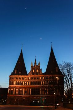 Venus, Jupiter and the crescent Moon over the Western city gate of Lubeck, Germany.