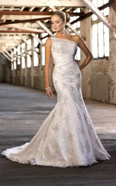 This dress looks like a one shoulder dress but it's a jacket that you see over a strapless gown for 2 different looks by Essense of Australia - Style D1209