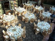 Overview of the eye catching gold chair covers and white satin pintuck linens, crystals
