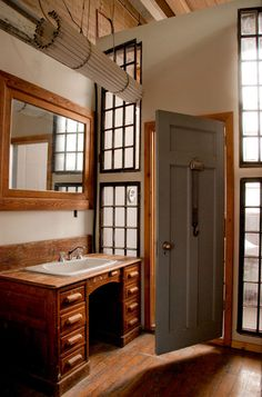 Rustic bathroom using old desk and other pieces for the vanity