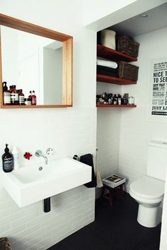LOVE LOVE LOVE THAT MIRROR!! THAT SHELF-FRAME IS SO COOL!  //   like general feel... the wood takes edge off of a more industrial/cold bathroom.... love protruding wooden frame on the mirror, shelves and typography poster