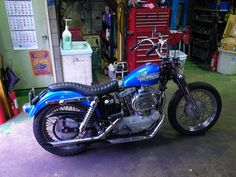 blue ironhead sportster swingarm custom with tuck and roll seat, drag pipes and fork boots by Shix Customs