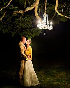 Elegant lighting hanging from the trees for an outdoor reception