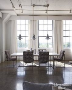 Ultrasuede curtains frame grey-painted sash windows, B Italia Athos dining table and vintage industrial pendants from Obsolete in Los Angeles. Milo Baughman chairs were re-covered in a Schumacher chevron.