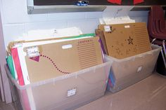 Cardboard class folders with color coded table folders inside (colored folders made from stapled roll paper)