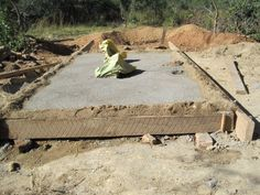 10. Cement is poured over the sheeting to make a slab. The cement slab - which has holes for the long-drops and ventilation pipes - must be watered for several days to prevent it from drying too quickly and cracking.