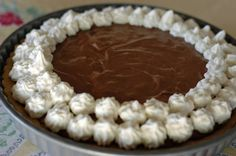 Chocolate mousse pie with toasted almonds in an almond crust, topped with real whipped cream