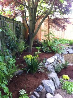 Mulched raised flower bed with rock wall
