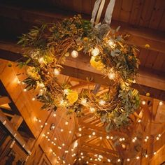 A large chandelier decorated with flowers and greenery and hung from the ceiling during the reception. #veryhitched