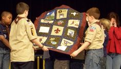My finished scout quilt after the many inspirational photos compiled on my pinterest board:)  I had each scout write a note or a drawing of what they liked best about scouting.  I scanned them and then printed it out onto iron on paper and used fused them onto blocks.  I purchased appropriate patches that our boys accomplished and put them on blocks as well. quilt idea, scout quilt