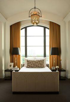 Barrel vaulted ceiling, window behind bed