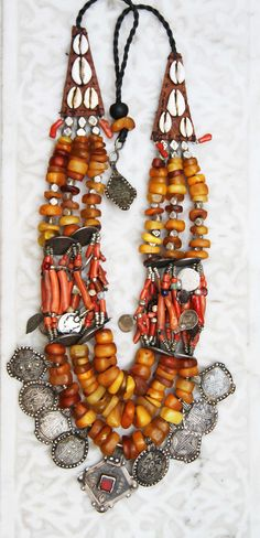by contemporary Marrakech designer Faouzi | Necklace incorporating amber, coral, silver, treasure pendants, shell, leather, cord, bone. | © Susan Storm ~ Savanna Caravan.