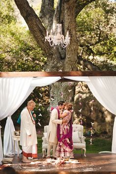 Wooden outdoor mandap with white draping, vintage sofa and chandelier via IndianWeddingSite.com