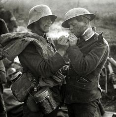 British and German soldiers exchange cigarettes, gifts, and addresses during Christmas Truce, 1914.