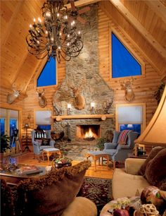 every log cabin house must have a fireplace!!! don't necessarily love the decor, but i love the fireplace, chandelier and the large windows