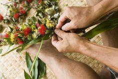 Master lei maker, Kilohana Domingo making a braided lei of lehua flowers .